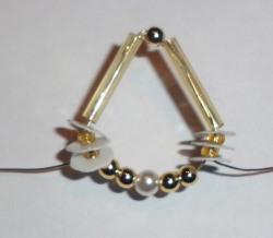 Zieht dann den Draht durch den Stift, die kleinen Perlen und die Plättchen nach unten zurück.
